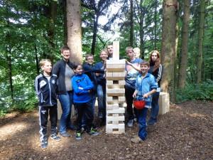 Eine Teamaufgabe war es aus einem Turm aus Holzklötzern einzelne Klötze zu entfernen und oben aufzulegen, sodass ein möglichst hoher Gruppenturm entstehen sollte.